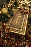 Christianity in Christmas. Bible with selective focus on the cross placed around Christmas ornaments Stock Image