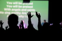 Christians Worshipping at Church. Christians raising their hands at a church worshipping Jesus during their religious service gathering Royalty Free Stock Image