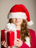 Christimas suprise. Beautiful smiling woman opening her christmas gift Royalty Free Stock Photography