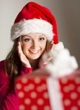Christimas suprise. Beautiful smiling woman opening her christmas gift Stock Photos