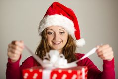 Christimas suprise. Beautiful smiling woman opening her christmas gift Stock Image