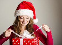 Christimas suprise. Beautiful smiling woman opening her christmas gift Royalty Free Stock Photos