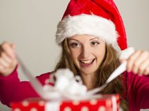 Christimas suprise. Beautiful smiling woman opening her christmas gift Royalty Free Stock Images