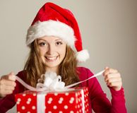 Christimas suprise. Beautiful smiling woman opening her christmas gift Stock Images