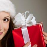 Christimas suprise. Beautiful smiling woman opening her christmas gift Stock Photos