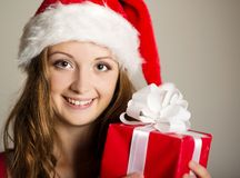 Christimas suprise. Beautiful smiling woman opening her christmas gift Stock Photo