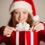 Christimas suprise. Beautiful smiling woman opening her christmas gift Royalty Free Stock Image