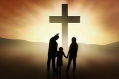 Christliche Familie, die am Kreuz steht Stockbilder