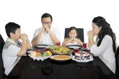 Christliche Familie, die vorher zu Mittag essen betet lizenzfreie stockfotos