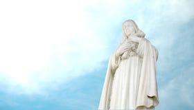 christliche Mönch-Marmorstatue, die Kreuz anhält Stockfoto