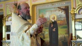 Christlicher Priester in den festlichen Kleidungsgesprächen mit einem Kreuz in seinen Händen stock video footage