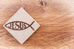 Christliches Fischsymbol schnitzte im Holz auf hölzernem Hintergrund der weißen Weinlese Stockbild