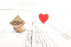 Christliches Fischsymbol schnitzte im Holz auf hölzernem Hintergrund der weißen Weinlese Lizenzfreies Stockfoto