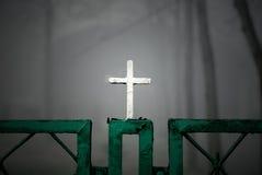Christliches Kreuz auf Zaun Stockfotografie