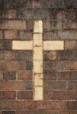 Christliches Kreuz in der Backsteinmauer stockfotografie