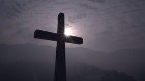 Christliches Kreuz mit Sonnenuntergang im Hintergrund lizenzfreie stockfotos