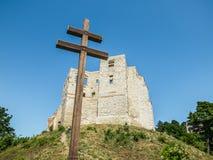 Christliches Kreuz und Ruinen eines alten Schlosses Stockfotografie