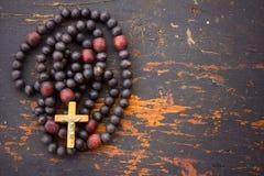 Christliches Rosenbeetgebet mit einem Kreuz auf altem schwarzem hölzernem Hintergrund stockfotografie