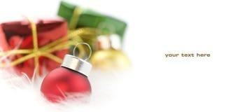 Christmas. Balls and gift boxes on white feather Stock Photos