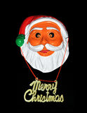 Christmas. Santa clause mask with merry christmas banner in black background Royalty Free Stock Photo