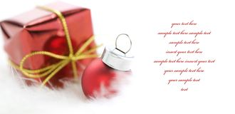 Christmas. Ball and gift box on white feather Stock Photo