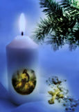 Christmas. A religious candle with Catholic cross and pine-tree in special Christmas blue lightning royalty free stock image