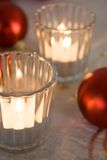 Christmas. Red Christmas ornaments and candles in glasses Royalty Free Stock Images