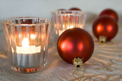 Christmas. Red Christmas ornaments and candles on table Stock Photography