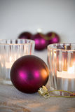Christmas. Purple Christmas ornaments and candles on table Royalty Free Stock Image