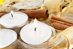 Christmas. Candles on random background with ribbons and cinnamon Stock Image