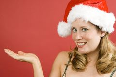 Christmas. Young woman on a red background wearing a Christmas hat holding hand out Stock Images