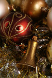 Christmas. A few pieces of Christmas decoration - a bell in the front and a couple of balls in red, gold and silver, with glittering background Stock Photography
