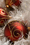 Christmas. A few pieces of Christmas decoration - dark red balls in white glittering string Stock Image