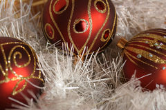 Christmas. A few pieces of Christmas decoration - balls and a bell in white, red, gold and silver, with glittering background Stock Photo