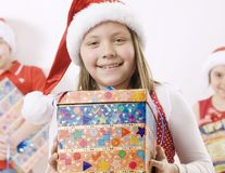 Christmas. Girl wearing santa hat with a gift, there are some kids in the background Stock Photography