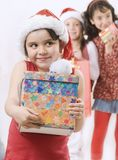 Christmas. Girl wearing santa hat with a gift, there are some kids in the background Stock Images