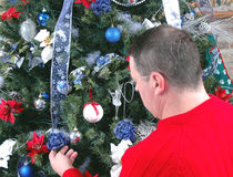 Christmas. Man decorating his christmas tree stock images