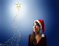 Christmas. Young woman wearing santa claus hat and a comet Stock Images