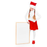 Christmas. Young girl with christmas cap Stock Images