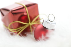 Christmas. Ball and gift box on white feather Royalty Free Stock Photos