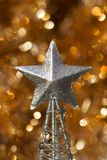 Christmas abstract. Silver Christmas star decoration on golden background Royalty Free Stock Photography