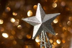 Christmas abstract. Silver Christmas star decoration on golden background Stock Images