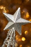 Christmas abstract. Silver Christmas star decoration on golden background Royalty Free Stock Image