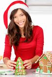Christmas activities - gingerbread house. Christmas activities - girl making gingerbread house. Young woman in Christmas preparations putting icing on stock photography
