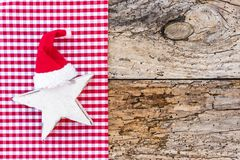 Christmas and Advent background, with white star shape and red santa hat on rustic background royalty free stock photos
