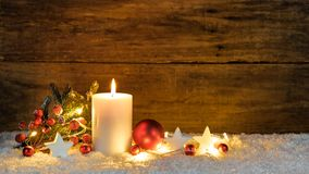 Christmas or Advent candle with red and white christmas ornaments and festive light royalty free stock photo