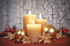 Christmas advent candles with golden and red decorations. Three burning candles with golden, red and green Christmas decorations on rustic neutral background Stock Image