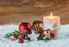 Christmas or Advent decoration with candle and snow. Christmas or Advent greeting card with burning candle on snow, decorated with fir branches, pine cones and Royalty Free Stock Images