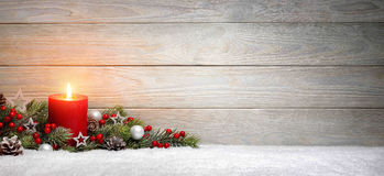 Christmas or Advent wood background with a candle. Christmas or Advent wood background with a burning candle on snow, decorated with fir branches and ornaments Royalty Free Stock Photos