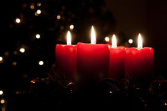 Christmas advent wreath with burning candles. Christmas advent wreath with red burning candles. Lights on x-mas tree in background Royalty Free Stock Photography
